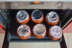 Six brown ceramic pots with baked or stewed food in the oven. Low DOF. Top view.