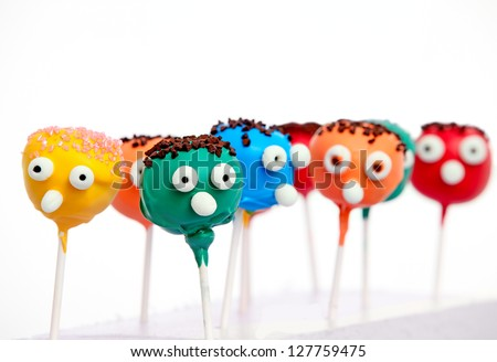 Six cake pops with funny faces isolated on white background