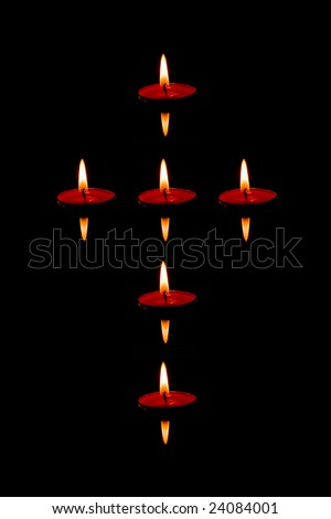 Six candles floating on the water shaped as cross