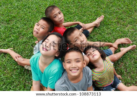 Six children playing in the park. - stock photo