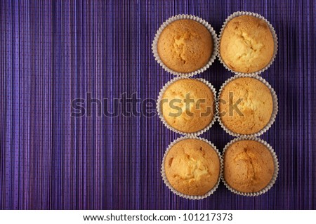 Six cupcakes on wooden mat with copy space. Top viewpoint.