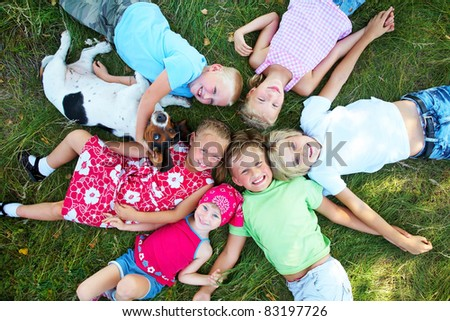Six  cute children and dog lying in green grass and enjoying summertime