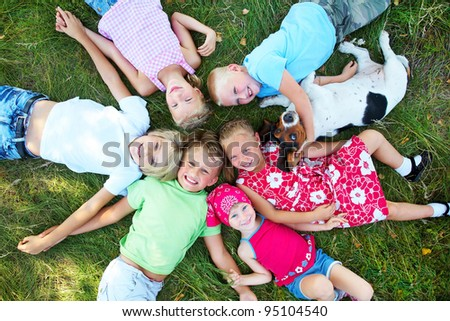 Six  cute children and dog lying in green grass and enjoying summertime - stock photo