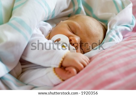 Six days old infant sleeping with her dummy.