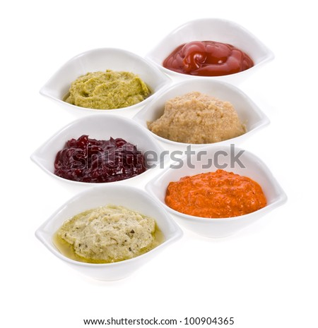 Six different sauces in a white bowl with spoons different colors on the horizontal surface isolated on white background