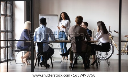 Six diverse businesspeople gathered in modern board room, different age ethnicity workers listen african woman coach tell about strategy, reporting using flip chart. Training and negotiations concept