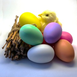 six Easter colored eggs a bundle of firewood and a chicken on a light background. High quality photo