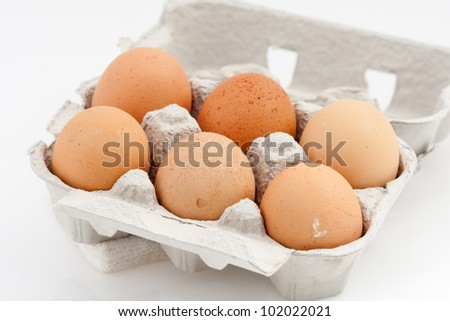 six eggs in a carton box isolated on white background