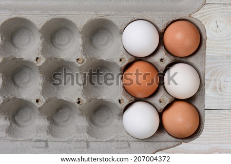 Six Eggs, three white and three brown, in a large carton with empty spaces. The carton is on a white farmhouse style wood kitchen table.