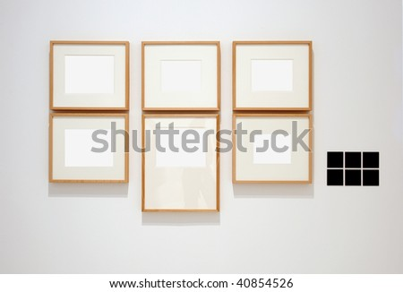 Six empty frames on white wall in museum with labels