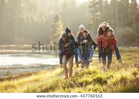 Six friends have fun piggybacking in the countryside by lake