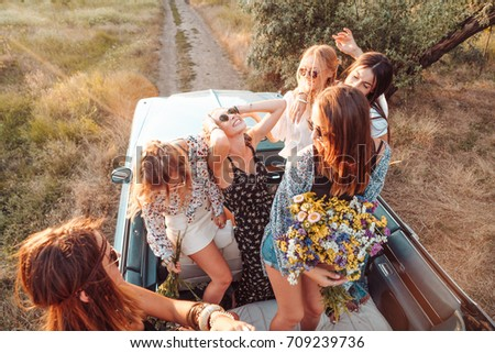 Six girls have fun on the car in the countryside