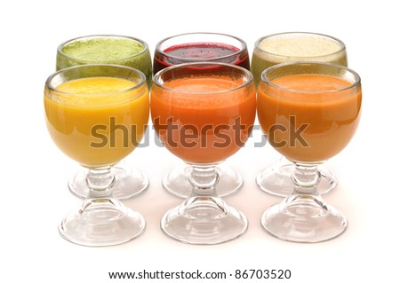 Six glasses of colorful fruit juices on white background