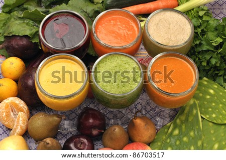 Six glasses of fresh juices surrounded by raw ingredients