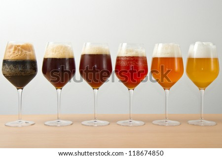 Six glasses with different beers on wooden table
