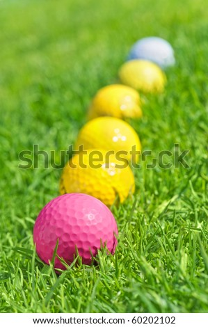 six golf balls on the green grass.Focus on the pink one.