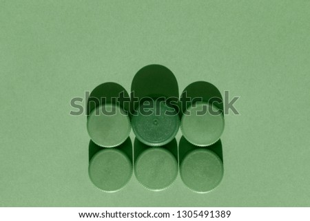 Six green plastic bottle caps on a green background, the round caps are in two rows , monochromatic effect #1305491389