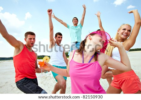Six joyful friends dancing on beach during vacation