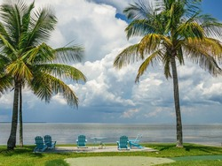 Six light blue Adirondack chairs, four in sunlight, by a small table between palms with a seaside view along the shore of a barrier island on the Gulf Coast on a cloudy afternoon in southwest Florida