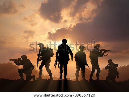 Six military silhouettes on sunset sky background