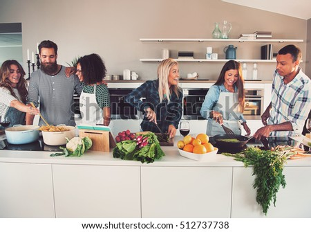 Six mixed Black and white friends preparing vegetables and pasta at long table in kitchen