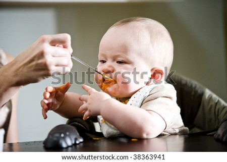Six month old baby eating solid food from a spoon