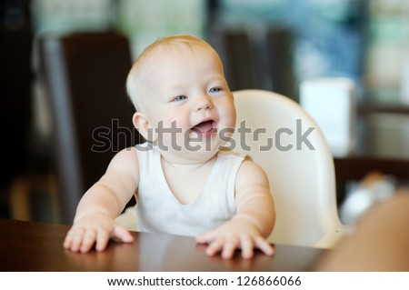 Six month old baby girl sitting by the table #126866066