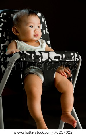 Six month old South East Asian Chinese baby girl sitting in a high chair