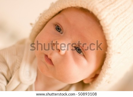 six months baby face with white hat indoor playing