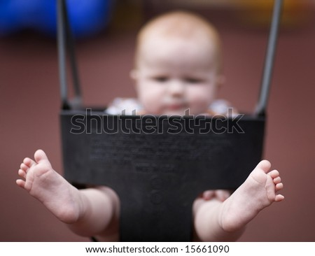 six months -old girl on a swing in the playground  - baby feets