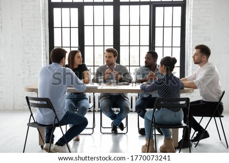 Six multi racial young and skilled employees gathered in boardroom sit at desk share ideas involved at corporate briefing. Team leader or coach express opinion teach staff at business training concept