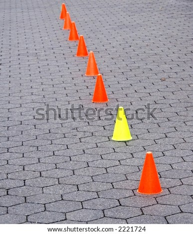Six orange and one yellow caution cones on a path made of hexagonal blocks in Central Park in New York City.