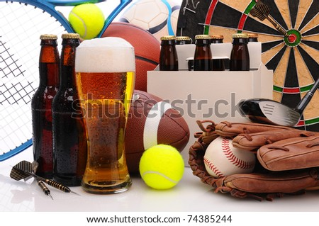 Six pack of beer and frothy glass surrounded by sports equipment. Horizontal Format Filling the frame. Sports represented include, football, basketball, soccer, darts, baseball, tennis and golf.