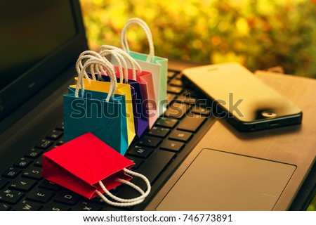 Six paper shopping bags and smartphone on notebook keyboard. business concept about online shopping or order goods on the internet It is more popular nowadays.  can buy everything from home or office