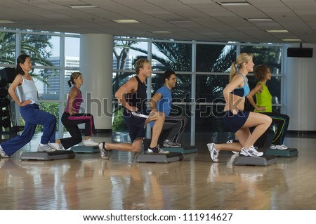 Six people exercising on step in aerobics class