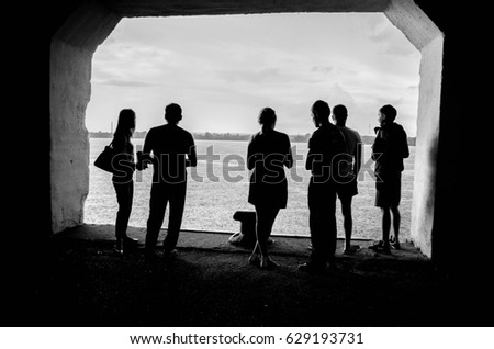 Six people under the bridge waiting till the rain is over #629193731