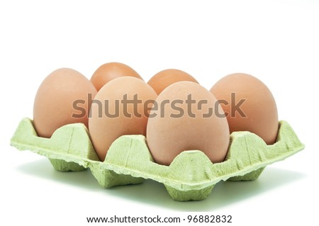 Six raw eggs in an egg cup on white background