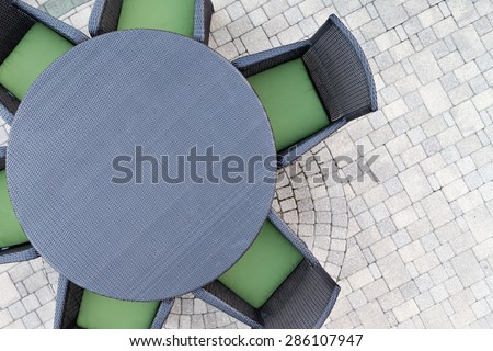 Six seater outdoor patio set with comfortable green cushions and a round dining table on a brick paved open-air patio with copy space, overhead view