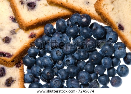 Six slices of blueberry bread surround a pile of fresh, wild blueberries on a white, isolated background.