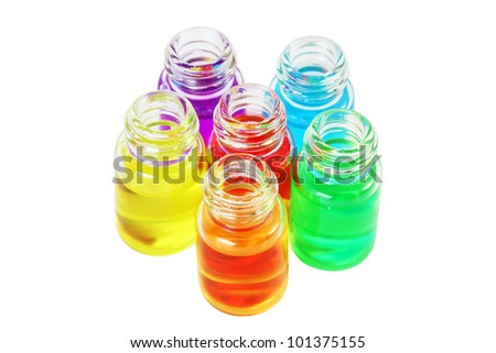 Six small bottles of different colored aromatic oils isolated on white background