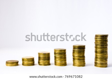 Six stacks of coin in ascending order on white gray background. Photo illustration of success in business and commerce, growth of revenue, investment, wage,  rising prices for goods, services #769671082