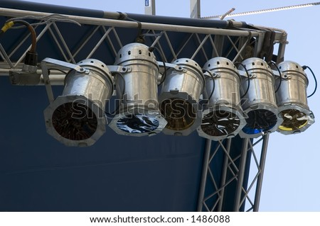 Six stage lights with color gel filters hanging by corner of outdoor stage