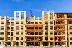 Six storey frame building under construction on concrete foundation bed
