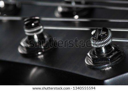 Six String Bass guitar head with Strings and Machineheads Closeup.