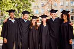 Six successful joyful multi ethnic attractive young graduates in black robes and hats finished their education, are smiling and bonding, behind is the collage building, nice sunny summer  day