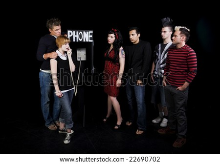 Six teenagers in a high school play.  A group of teenagers wait for their turn to use a public phone, while another girl hogs it.