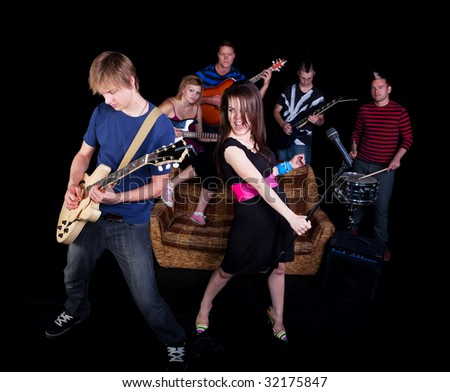 Six teens in a high school rock band practicing on a stage. - stock photo