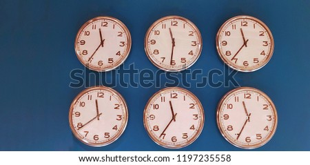 Six wall clocks with twelve hour clock face on blue background