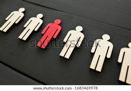Six wooden persons on the table and one person is painted in red color. The concept of coronavirus or another virus is spreading to people. Foto stock ©