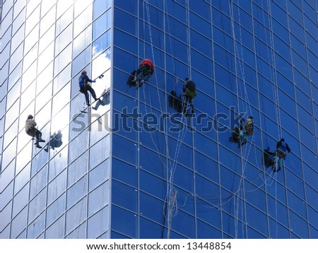 Six workers washing windows in the office building